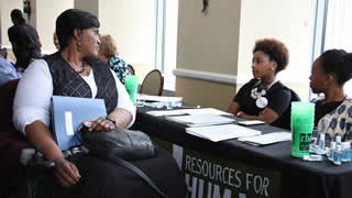 Academy student Paula Smith discussion job opportunities with Resources for Human Development representatives Julicia James and Taylor Thompson